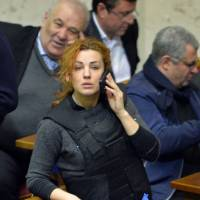 Chamber and bullets: Lesya Orobets, a deputy of the opposition Fatherland party of jailed former Prime Minister Yulia Tymoshenko, wears a bulletproof vest during an extraordinary session of the Ukrainian parliament on Jan. 28. On the eve of the session, she wrote on Facebook that she would not be attending, 'as there is not the slightest certainty that after entering the chamber I would be able to get out.' She dismissed concessions by the government to ease the crisis as 'tricks for spectators' and 'tactical steps.' | AFP-JIJI