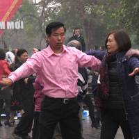 A Vietnamese couple ballroom dance close to a statue in Hanoi on Sunday. Anti-China protestors hoping to lay wreathes at the statue said they believed the dancers were deployed by the government to stop them gathering there. | AP