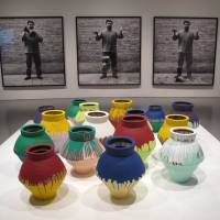 This October 2012 photo shows work by Chinese artist Ai Weiwei, with pictures of him smashing one of the painted ancient vases in the foreground, at the Hirshhorn Museum in Washington. | AFP-JIJI