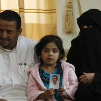 Afnan, age 6, holds a picture of her father, Bandar al-Hassani, who was killed in a U.S. drone strike last year, on Feb. 14. Beside her are her grandparents Omar al-Hassani and Khadija Hassan. Beside Bandar, the couple have lost two more sons: one in another U.S. drone strike in 2013 and one during fighting between al-Qaida militants and government forces in 2012. | AP