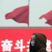 A woman wearing a protective mask walks through Tiananmen Square during a hazy day in Beijing on Feb. 13. The city issued a rare 'orange' alert Friday, the second-highest of the four levels of urgency, prompting health advisories and bans on barbecues, fireworks and demolition work, but no order to pull cars from the streets. | AP