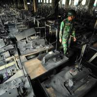 Gutted: A member of the Bangladeshi Army walks through the nine-story Tazreen Fashion plant in Savar, about 30 km north of Dhaka, in November 2012 after a lethal blaze. | AFP-JIJI