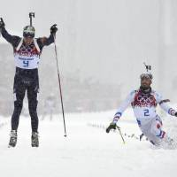 Norway's Emil Hegle Svendsen (left) and France's Martin Fourcade race to the finish line  in the men's biathlon 15-km mass start event in Rosa Khutor, Russia, on Tuesday. Svendsen won the gold. | AFP-JIJI