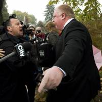 Patience cracks: Toronto Mayor Rob Ford tells reporters to get off his property as he leaves his home in Toronto on Oct. 31. | AP