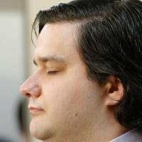 Mark Karpeles, chief executive officer of the troubled Mt. Gox bitcoin exchange, keeps his eyes closed during a news conference in Tokyo after the company filed for bankruptcy protection in Japan earlier the day. | AP