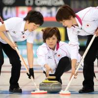 Here it comes: Ayumi Ogasawara throws the stone in Japan's round-robin match against Canada in women's curling on Saturday in Sochi, Russia. | AFP-JIJI