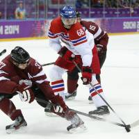 Competitive spirit: Latvia defenseman Oskars Bartulis (left) and Czech Republic forward Jaromir Jagr vie for the puck in the first-period action on Friday in Sochi, Russia. | AP