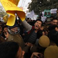 Outraged: Indian police stop a student during a protest in New Delhi on Saturday against the beating to death of university student Nido Tania from India's remote northeast, an incident that has sparked a furious outcry against racism and criticism of police. | AP