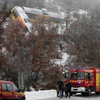 Nightmare ride: A two-car train hangs on the edge of a ravine after being derailed by a tumbling boulder that smashed into it outside the southeastern French town of Annot on Saturday. The popular train takes a leisurely three hours to travel the scenic 150 km from Nice to Dignes-les-Bains. | AP