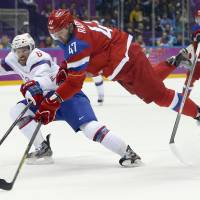 Dynamic force: Russia forward Alexander Radulov, making an off-balance shot against Norway defenseman Jonas Holos in the second period, contributes two goals and an assist in his team's 4-0 victory in the Olympic men's hockey tournament on Tuesday. | AP