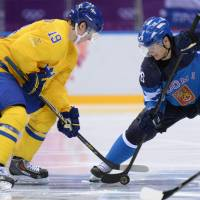 Heated rivalry: Sweden's Nicklas Backstrom (left) and Finland's Jussi Jokinen battle for the puck in the men's ice hockey semifinal match at the Bolshoy Ice Dome in Sochi, Russia, on Friday. | AFP-JIJI
