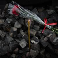 Resistance and passion: A candle and a rose lie on a stack of cobblestones at a barricade in Kiev on Saturday. | AFP-JIJI