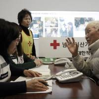 South Korean Lee Kyun-myoung, 93, (right) talks with Red Cross members as he fills out application forms to reunite with his family members living in North Korea, at the Korea Red Cross headquarters in Seoul last Thursday. | AP