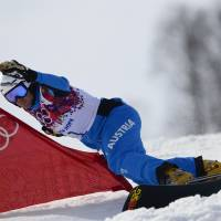 En route to third: Austria's Benjamin Karl races in the men's snowboard parallel slalom final at Rosa Khutor Extreme Park on Saturday. Karl earned the bronze medal. | AFP-JIJI
