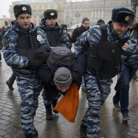 Silenced: Police officers detain a protester near Red Square during an unauthorized protest in Moscow on Saturday. Around 40 people gathered near Red Square to protest the decision of leading Russian cable and satellite companies to drop channel Dozhd (TV Rain). Opening up umbrellas together to play on the name of the TV station, most were immediately detained. | AP