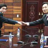 Again, it's a start: In this South Korean Unification Ministry photo, head of the South's working-level delegation, Lee Duk-haeng (right) greets North Korean counterpart Park Yong Il after they exchanged documents of a signed agreement at Tongilgak in the North Korean side of the Panmunjom border town Wednesday. | AP