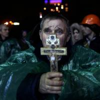 An anti-government protester holds a crucifix as he prays at Independence Square in Kiev on Thursday. | AP
