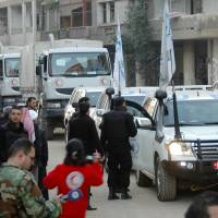 Fragile hope: A handout picture released by the official Syrian Arab News Agency (SANA) on Saturday purportedly shows a convoy of United Nations and Syrian Red Crescent vehicles waiting to enter the regime-held areas of the Syrian city of Homs. A convoy delivering aid to civilians trapped in the area was fired on and a number of people killed or wounded, raising questions about whether the hard-won humanitarian mission can proceed. | AFP-JIJI