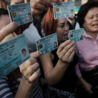 Disenfranchised: Thai people unable to cast votes in their district display their national identification cards and shout slogans as Thai police officers (not shown) secure and block a street leading to a polling station occupied by Thai anti-government protesters (not shown) in Bangkok on Sunday.AFP-JIJI
