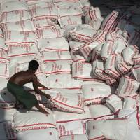 Rice try: A worker sorts rice bags inside a ship in Bangkok in September 2011. Angry farmers, a mountain of rice and a slew of corruption allegations — a flagship policy that helped propel Thailand's prime minister to power — now threatens to boomerang on her embattled government. | AFP-JIJI
