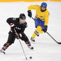 Drive to compete: Japan's Ami Nakamura controls the puck in front of Sweden's Josefine Holmgren in a women's ice hockey Group B contest on Sunday at Shayba Arena. Sweden defeated Japan 1-0. | AFP-JIJI