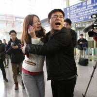A relative of a passenger onboard Malaysia Airlines flight MH370 cries as she talks on her mobile phone Saturday at the Beijing Capital International Airport. The Malaysia Airlines flight carrying 227 passengers and 12 crew lost contact with air traffic controllers early on Saturday en route from Kuala Lumpur to Beijing, the airline said in a statement.