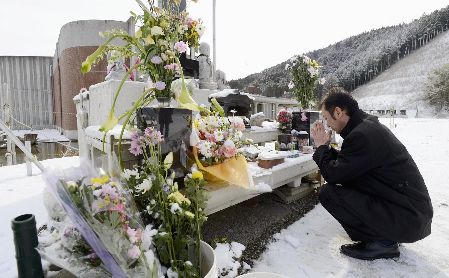Kazutaka Sato, the father of an elementary school student who perished in the March 11 tsunami in the city of Ishinomaki, Miyagi Prefecture, prays at a memorial in front of the school Monday before submitting a lawsuit with other parents demanding compensation from the city and prefectural governments.