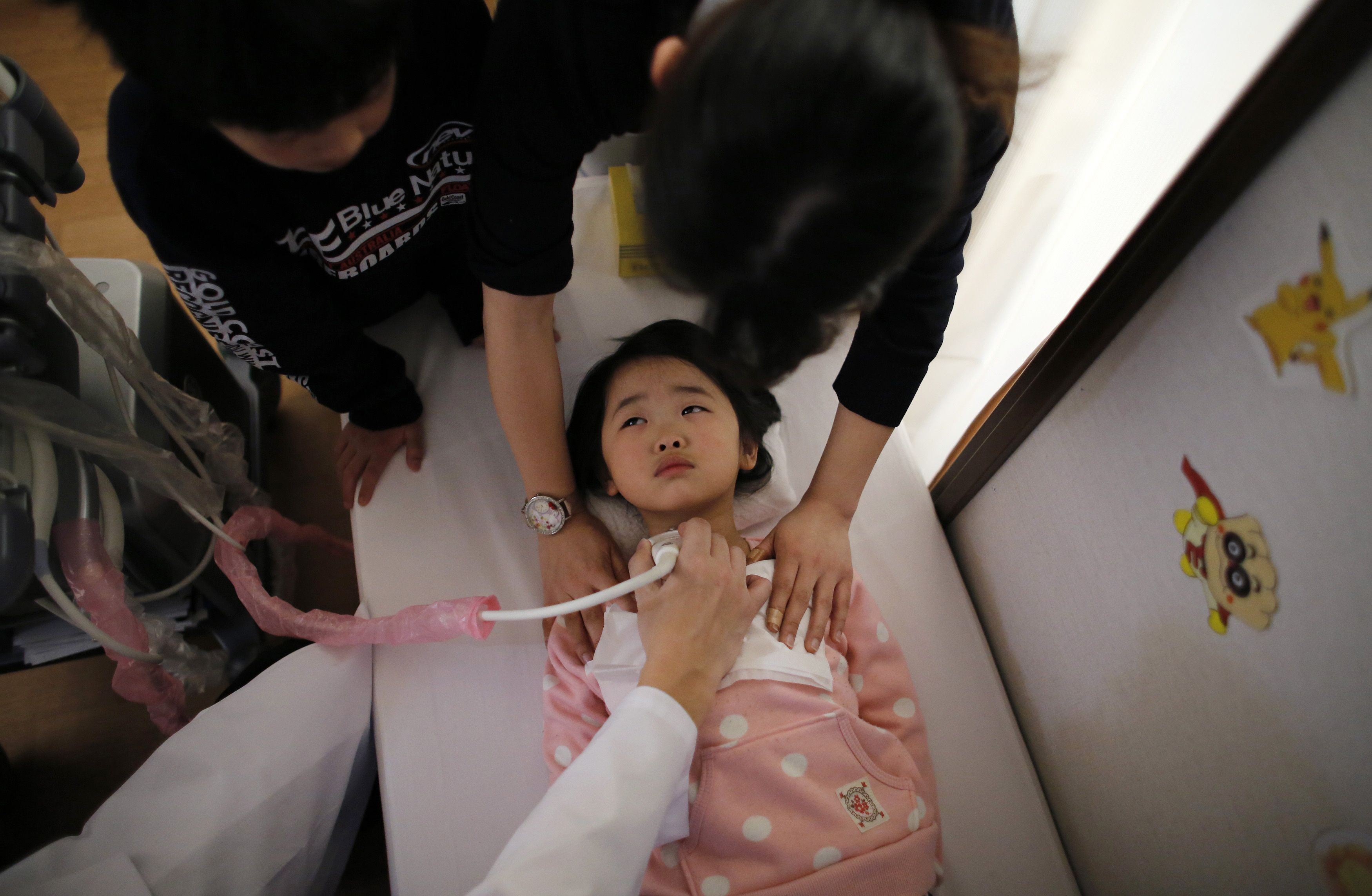 A doctor conducts a thyroid examination on 5-year-old girl as her older brother and a nurse take care of her at a clinic in temporary housing complex in Nihonmatsu, west of the tsunami-crippled Fukushima No. 1 nuclear power plant, on Feb. 27.