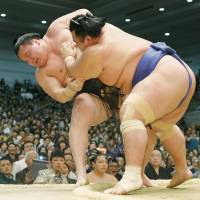 Show of force: Ozeki Kotoshogiku pushes out yokozuna Hakuho (7-6)  on Friday, the 13th day of the Spring Grand Sumo Tournament. Hakuho and promotion-chasing ozeki Kakuryu are tied for the lead at 12-1. The two will face off on Saturday.   | KYODO