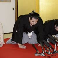 Kakuryu is flanked by stablemaster Izutsu (right) and his stablemaster's wife at Hoganji temple in Tennoji Ward, Osaka, on Wednesday upon being named yokozuna.  | KYODO