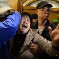 A relative of passengers on Malaysia Airlines flight MH370 cries after hearing the news at a hotel in Beijing on Monday that the plane plunged into Indian Ocean.  | AP