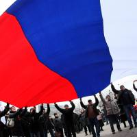 Pro-Russian protesters wave a giant Russian flag during a rally Saturday in Donetsk. More than 10,000 people protested in the eastern Ukrainian city of Donetsk, the stronghold of ousted president Viktor Yanukovych.    AFP-JIJI