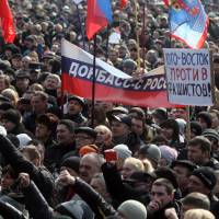 Pro-Russian protesters hold a banner (center) reading 'Donetsk region with Russia' and a placard reading 'South-east against fascism!' during a rally in Donetsk, Ukraine. | AFP-JIJI