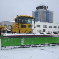 One of White Impulse's snowplows with the Aomori Airport terminal building in the background.