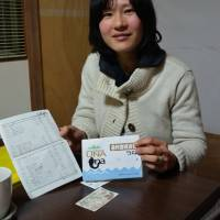 Member MikiSato shows her 'Una' checkbook, named after unagi (eel), a local delicacy. | WINIFRED BIRD