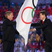 International Olympic Committee President Thomas Bach (left) hands the Olympic flag to Pyeongchang Mayor Lee Seok-rae during the closing ceremony of the Sochi Olympics on Feb. 23. | AFP-JIJI