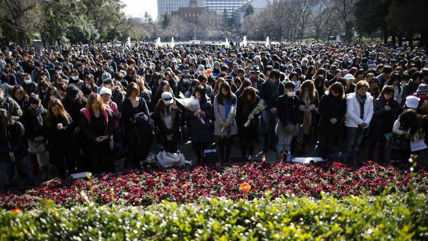 People at a rally in Tokyo on Tuesday observe a moment of silence at 2:46 p.m., the time the magnitude-9.0 quake struck off Tohoku in 2011.