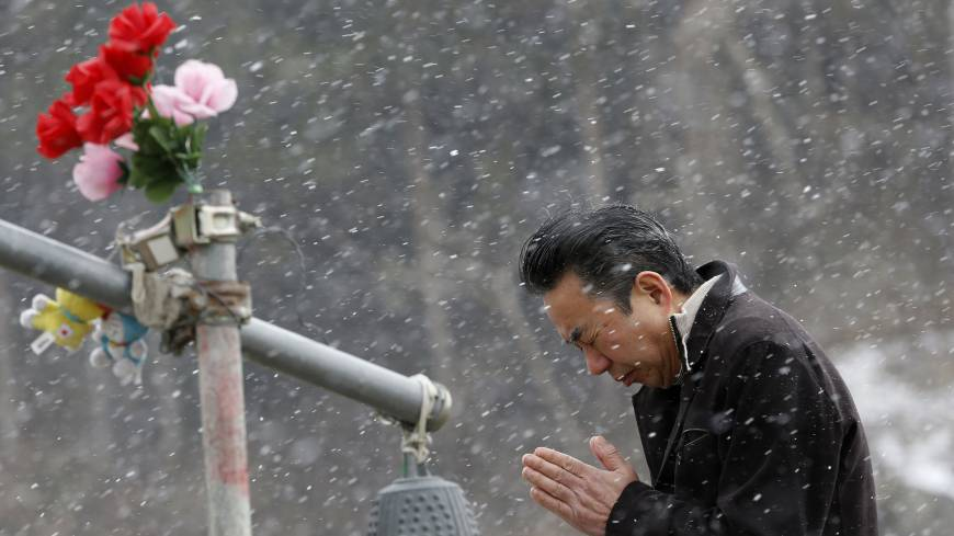 A man prays Tuesday in front of the main entrance of Okawa Elementary School in Ishinomaki, Miyagi Prefecture, where 74 of the 108 students went missing after the March 11, 2011, tsunami.