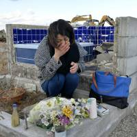 Makiko Suzuki, 41, cries Tuesday at the remains of her house in Iwaki, Fukushima Prefecture, where she had lived with her parents before they were killed by the tsunami. | KYODO