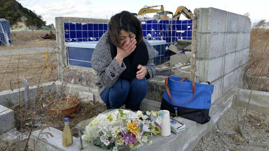 Makiko Suzuki, 41, cries Tuesday at the remains of her house in Iwaki, Fukushima Prefecture, where she had lived with her parents before they were killed by the tsunami.