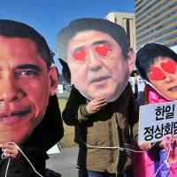 Activists don masks of U.S. President Barack Obama, Prime Minister Shinzo Abe and South Korean President Park Geun-hye in Seoul on Friday to protest their upcoming trilateral meeting. | AFP-JIJI