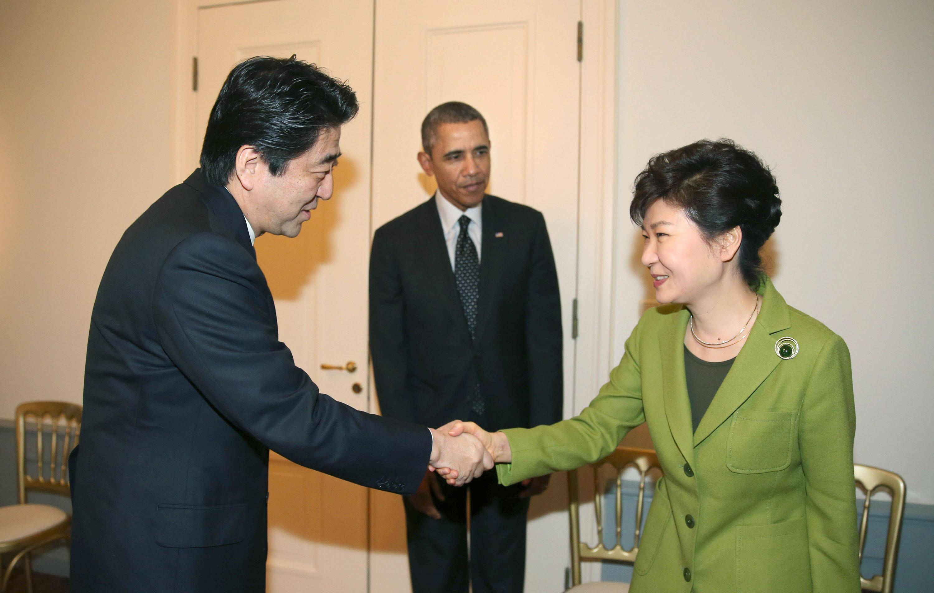 Prime Minister Shinzo Abe shakes hands with South Korean President Park Geun-hye on Tuesday in The Hague. | YONHAP/KYODO