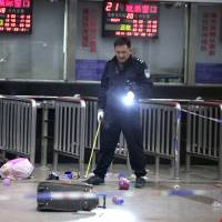 A police officer inspects the scene of an attack that left 33 people dead at southwest China's Kunming railway station late Saturday. | AFP-JIJI