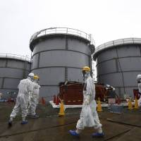 Tokyo Electric Power Co. employees in hazmat suits walk through the Fukushima No. 1 nuclear plant in November. | AP