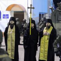 Orthodox priests stand with armed men, thought to be Russian troops, blocking a Ukrainian frontier guard base in Balaklava, near the Crimean port of Sevastopol, on Saturday. | AFP-JIJI