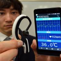 An employee of machinery maker NS West holds the 'Earclip-type Wearable PC,' which is equipped with a GPS, compass and barometer among other features, in Tokyo on Feb. 20. The device was developed by Kazuhiro Taniguchi of Hiroshima City University. | AFP-JIJI