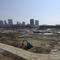 Power shovels operate in the Toyosu area of Tokyo on Sunday. Data released Tuesday shows that both residential and commercial land prices in major cities jumped in 2013. | BLOOMBERG