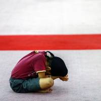 A person prays for Flight MH370 at a Sikh temple in Kuala Lumpur on Thursday. | REUTERS