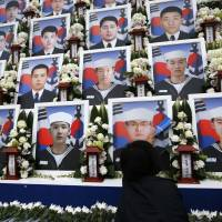 A woman touches her late son's portrait after an event Wednesday at the National Cemetery of South Korea in Daejeon to mark the fourth anniversary of the sinking of the Cheonan, which is believed to have been torpedoed by North Korea in 2010, killing 46 South Korean Navy sailors. | REUTERS