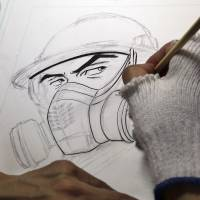 Manga artist Kazuto Tatsuta draws the main character in '1F: The Labor Diary Of Fukushima No. 1 Nuclear Power Plant' in his studio outside Tokyo on Monday. | AP